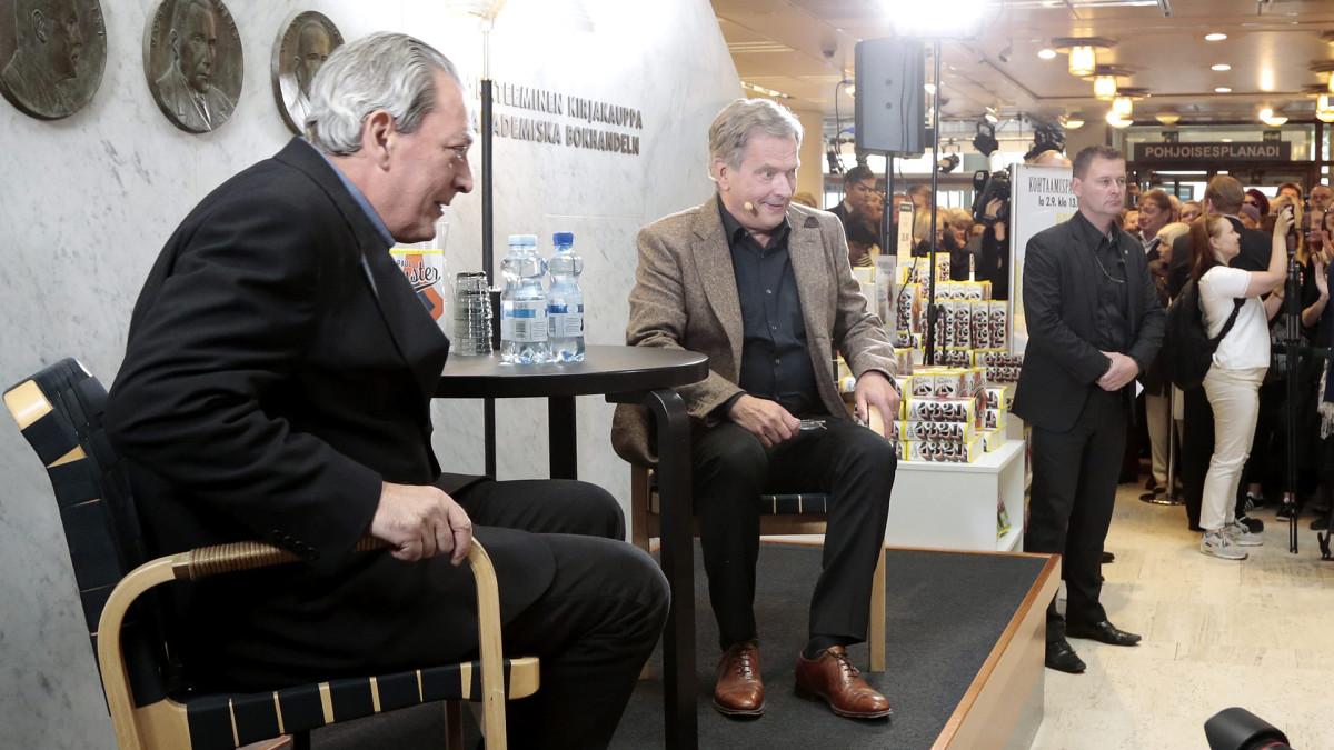 Presidentti Sauli Niinistö haastattelemassa kirjailija Paul Austeria Akateemisessa kirjakaupassa Helsingissä lauantaina.