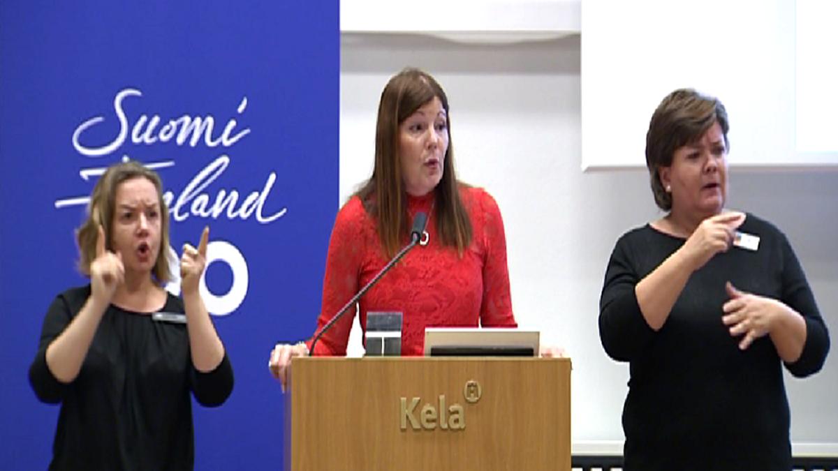 Kokoomuksen kansanedustaja Sari Sarkomaa molemilla puolillaan viittomakielen tulkki.