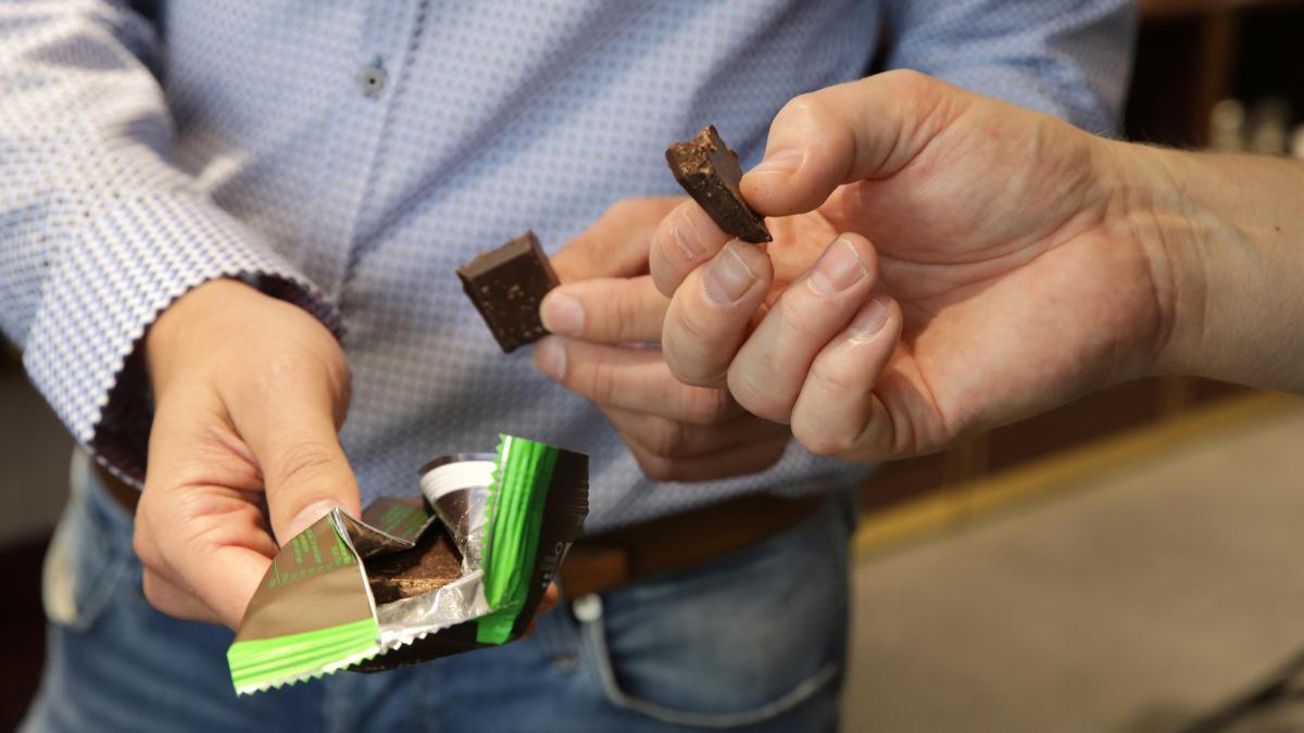 Suklaalevy ja suklaapaloja kahden miehen käsissä