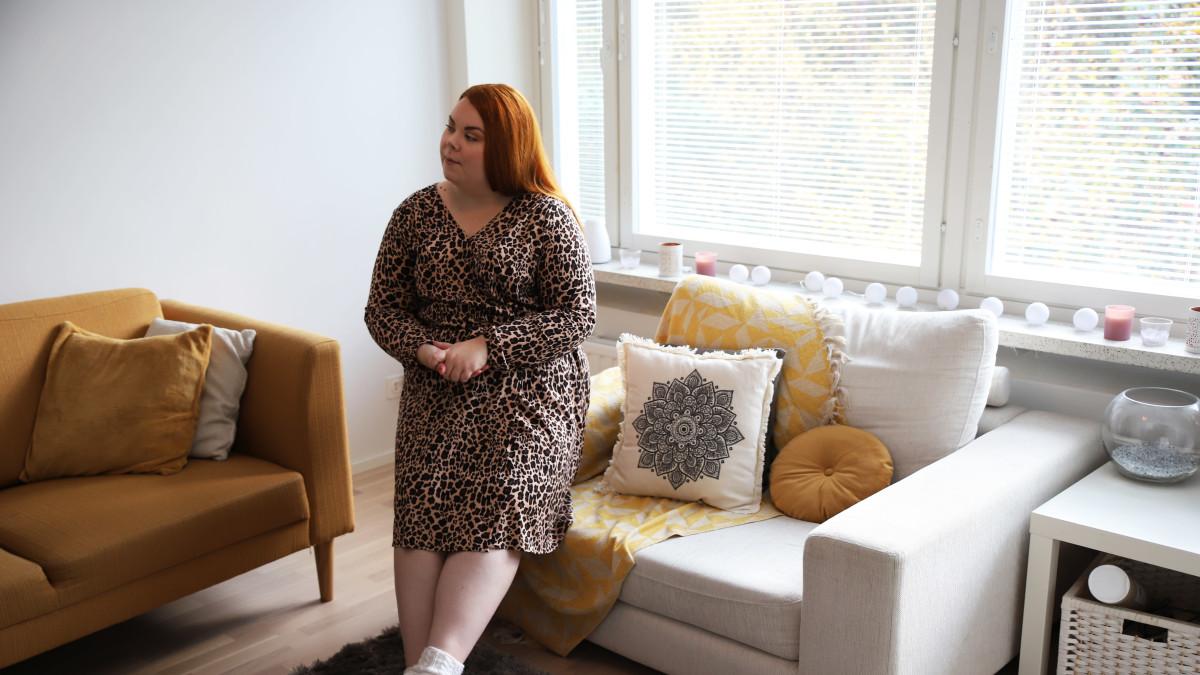 Krista Kohonen istumassa asuntonsa sohvalla.