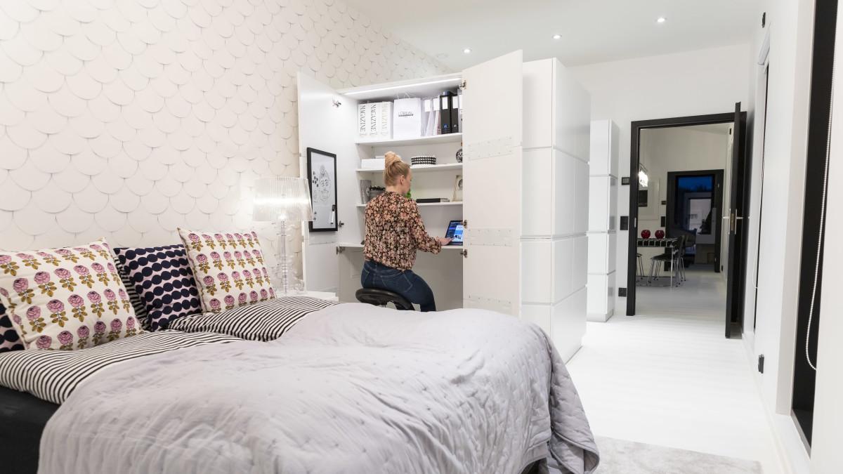 Etualalla sänky, jonka takana nainen tekee töitä kaappiin rakennetussa etätyöpisteessä.