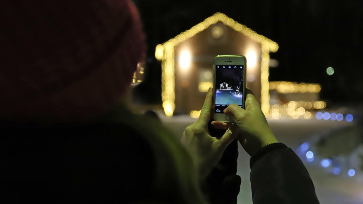 Nainen ottaa kännykkäkuvaa Mikkelin Emolassa sijaitsevasta talosta, joka on koristeltu jouluvaloilla.