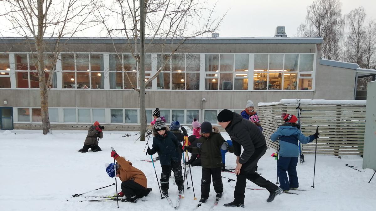 Ekaluokkalaiset hiihtotunnilla opettajansa kanssa.