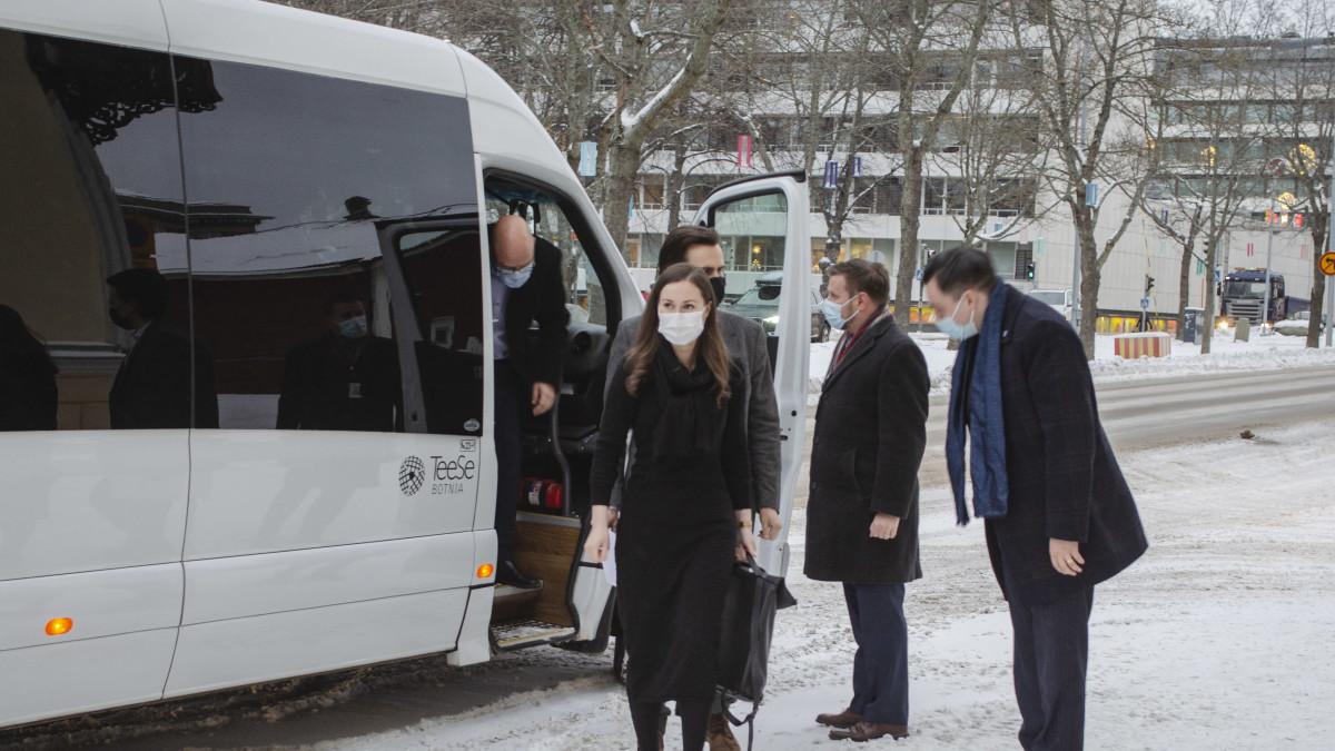 Kvinna klädd i svart kappa kliver ur taxi, följs av flera manspersoner klädda i mörka ytterrockar.