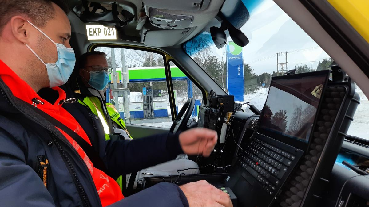 kaksi ihmistä istuu ambulansissa ja tutkii tietokonetta
