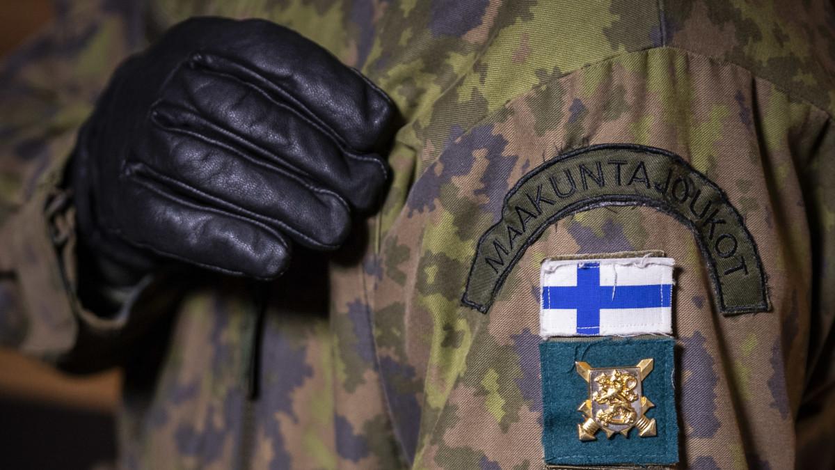 Hihassa siniristilippu ja maakuntakomppanian soikea merkki, missä kärppä ja viisi ristiä.