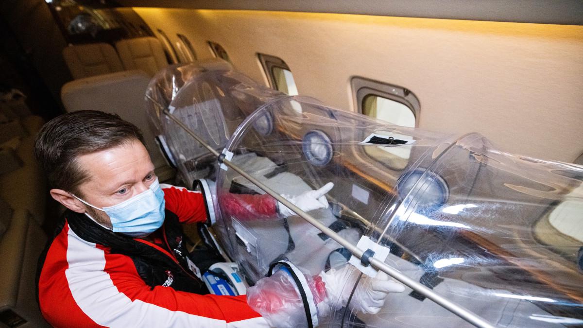 EMA Finlandin lääketieteellinen johtaja Tuomas Hiltunen esittelee eristysyksikköä lentokoneessa.