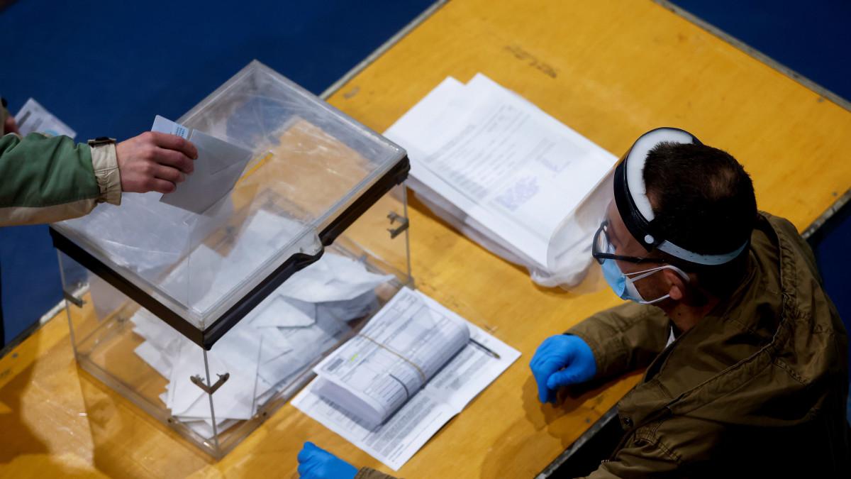 Äänestäjä pudottaa lipuketta vaaliuurnaan vaalivirkailijan edessä