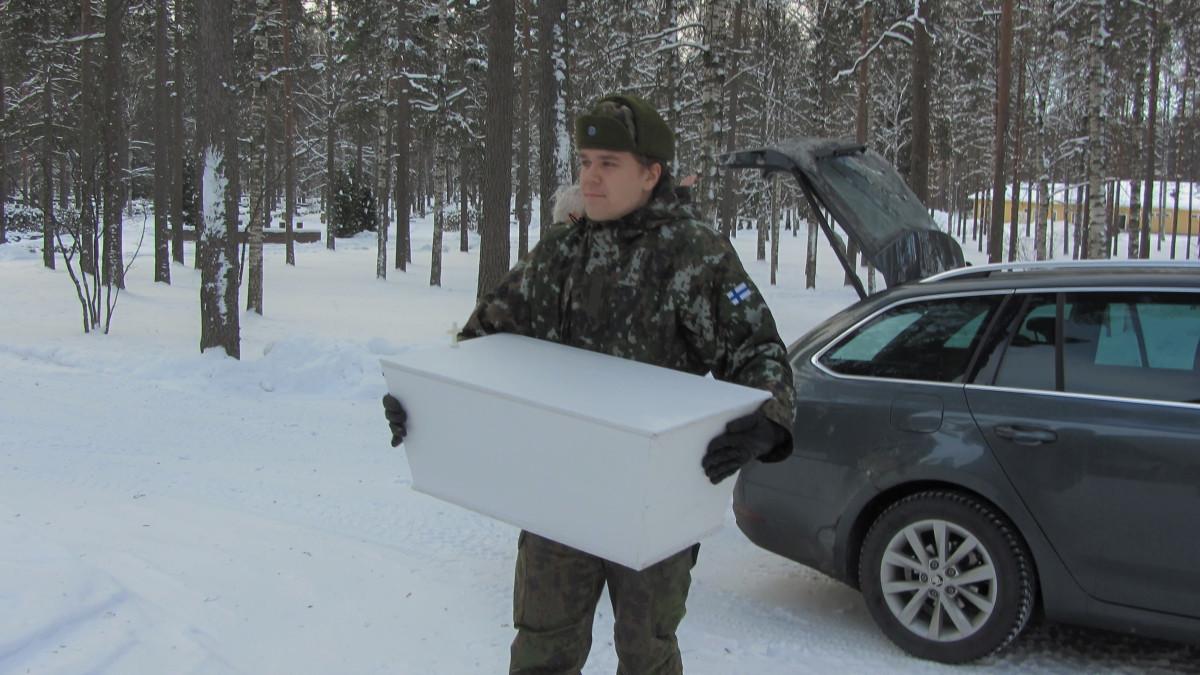 Kaartinjääkäri Joona Jakkola kantaa arkkua.