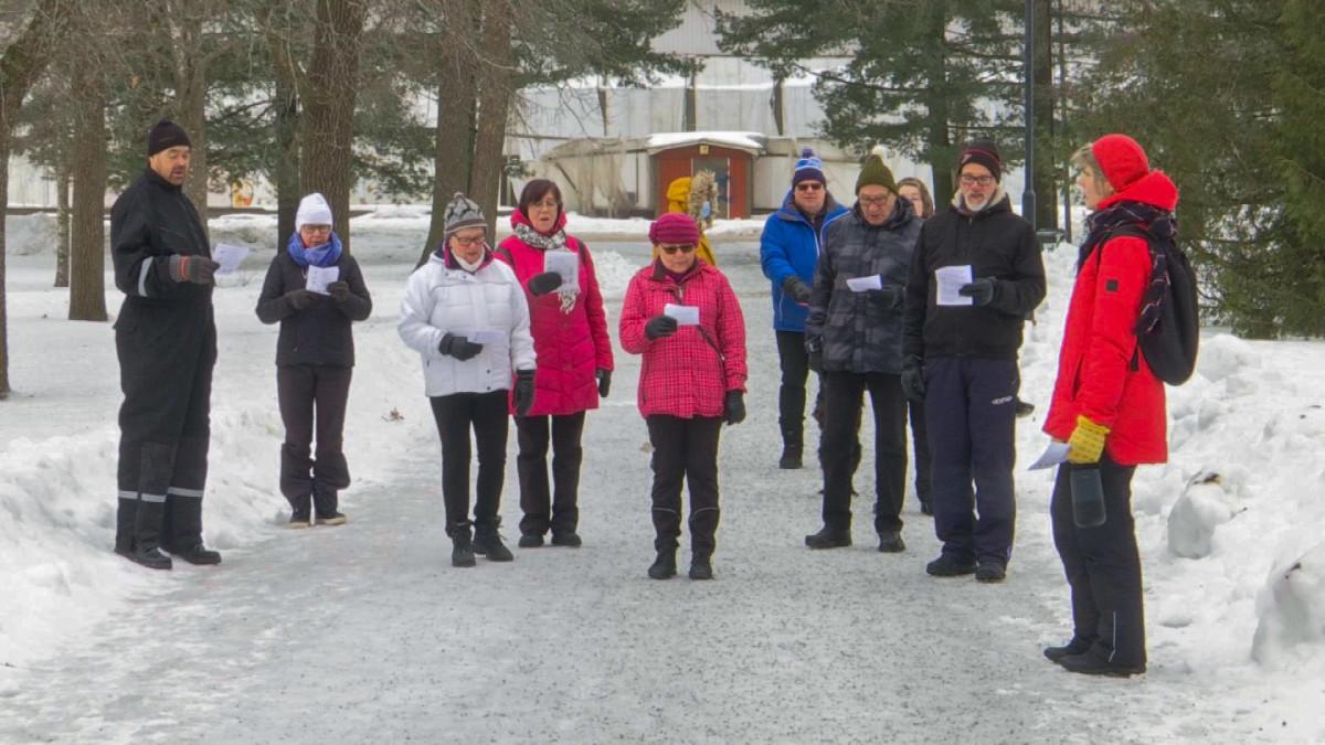 Ryhmä kuorolaulajia harjoittelee laulua lumisessa puistossa toppatakit yllään
