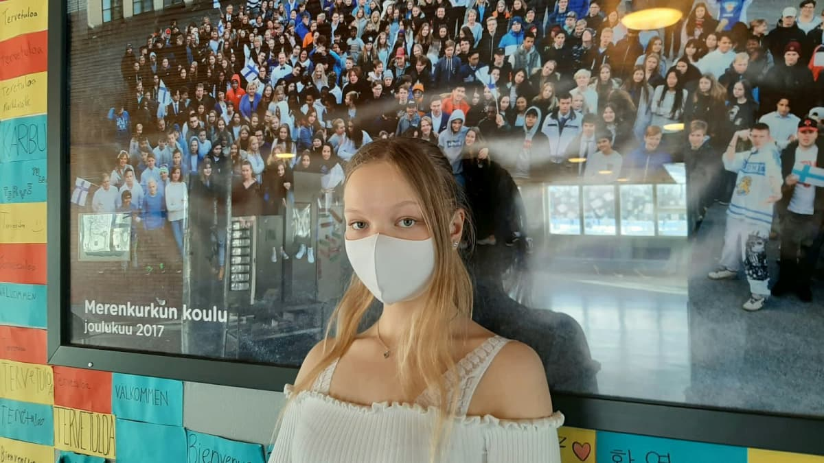 9-luokkalainen Selina Keski-Valkama seisoo koulun yhteiskuvan edessä.
