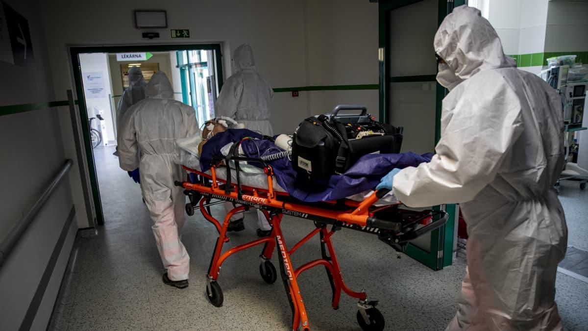 Suojapukuinen henkilökunta kuljettaa potilasta paareilla