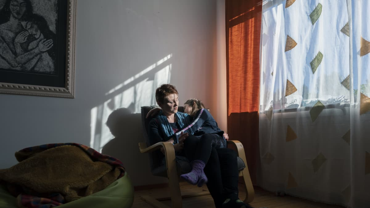 Nainen istuu tuolilla tyttö sylissään. Aringon valo ikkunasta valaisee naisen kasvot ja piirtää teräviä varjoja seinään.