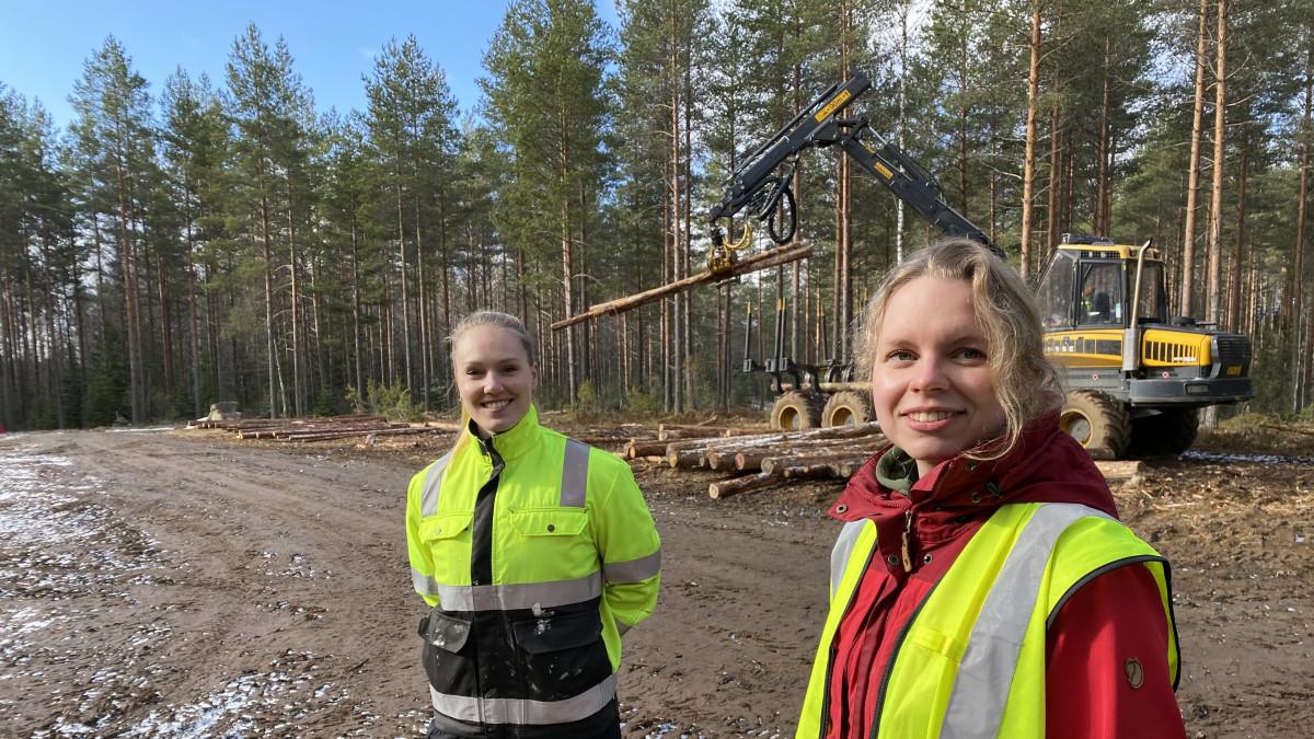Hämeen ammattikorkeakoulun metsäalan opiskelijat Reetta Huovinen ja Miia Makkonen metsässä moton edessä Lammin Evolla.