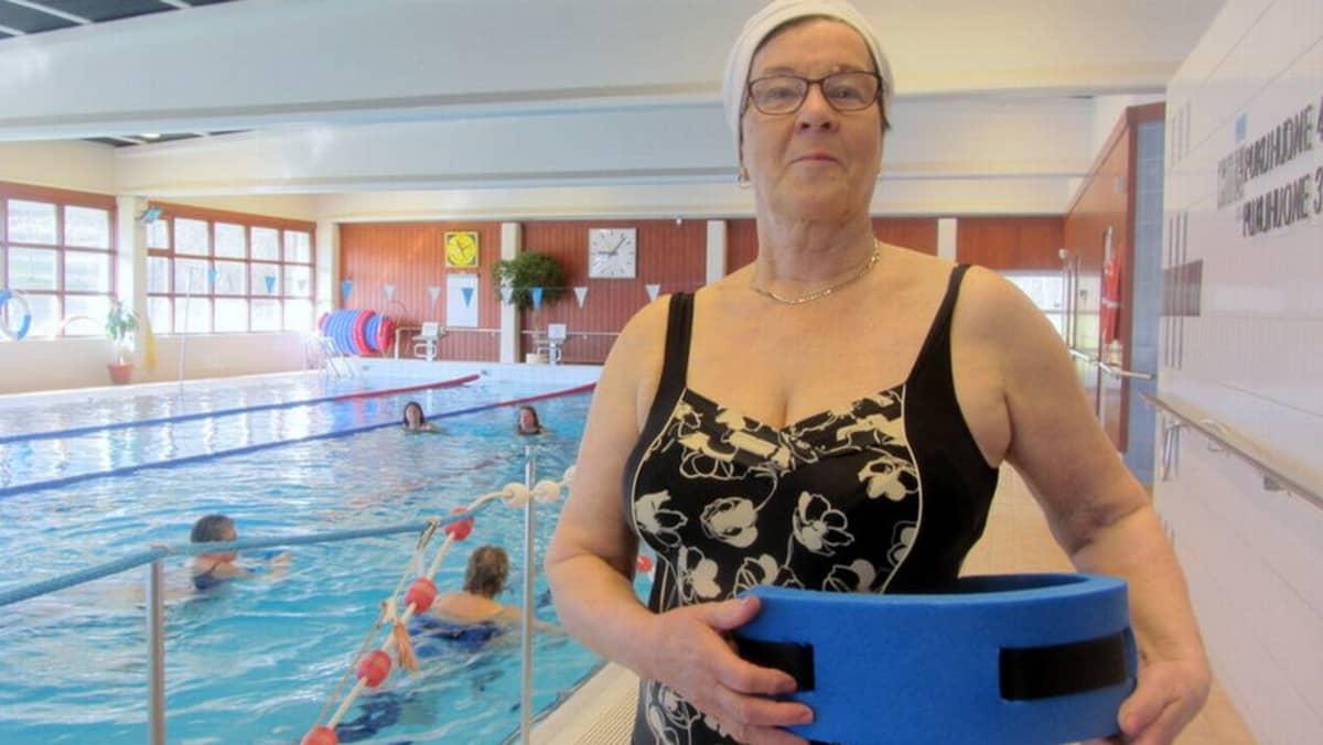 Nainen seisoo uimahallissa vesijuoksuvyön kanssa.