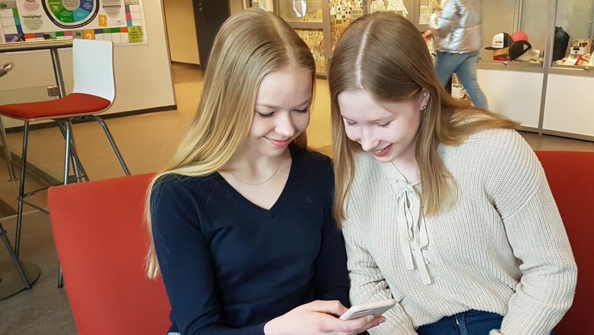 kaksi nuorta yhdeksäsluokkalaista kännyköidensä kimpussa