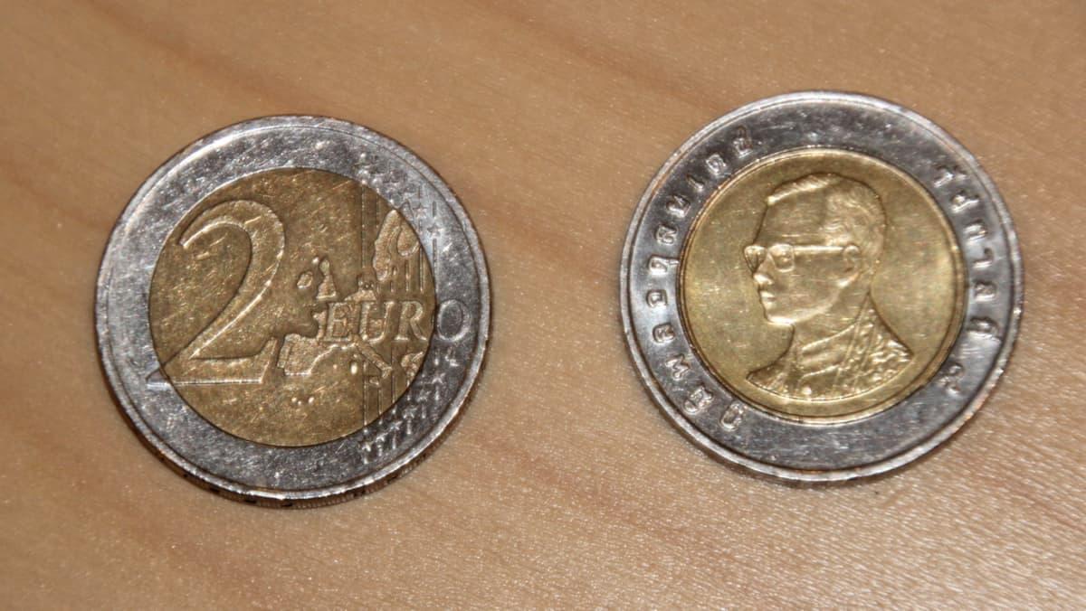 Kahden euron ja Thaimaan 10 bahtin kolikot vierekkäin