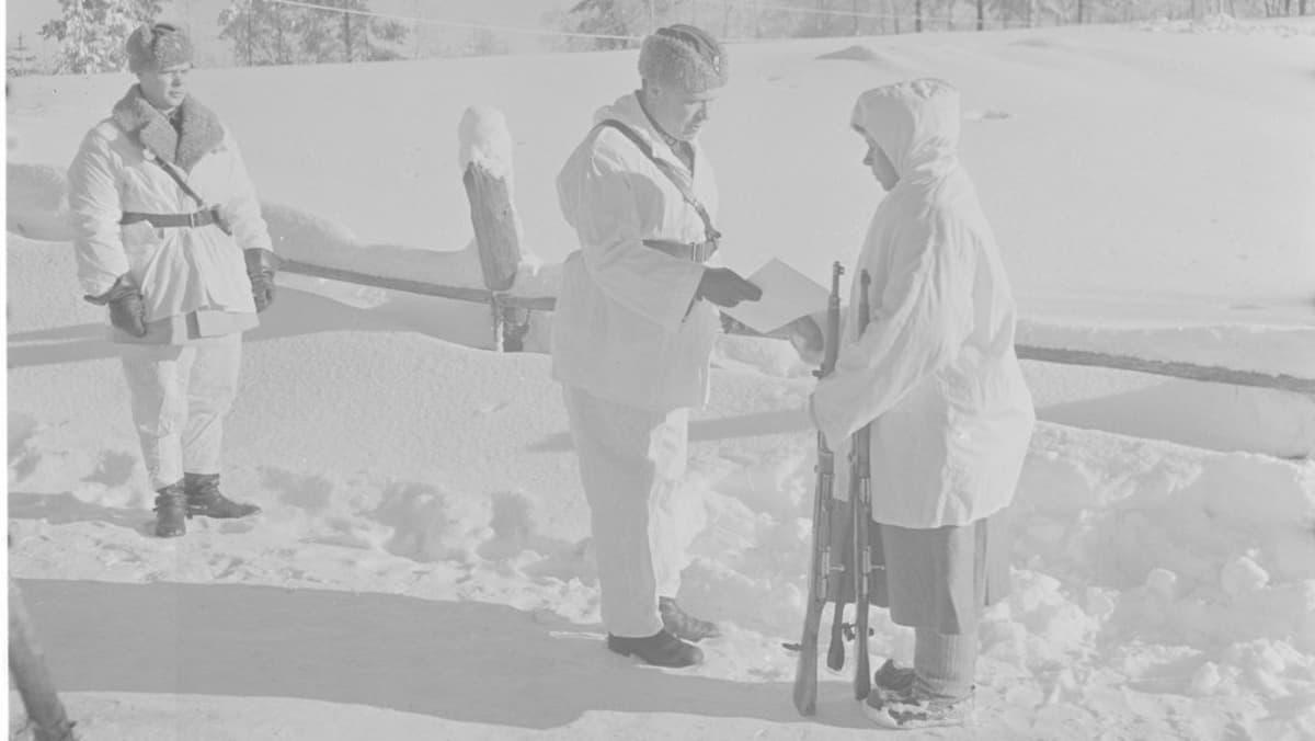 Eversti Svensson ojentaa Simo Häyhälle kiväärin ja kunniakirjan, jonka eräs ruotsalainen on lahjoittanut.