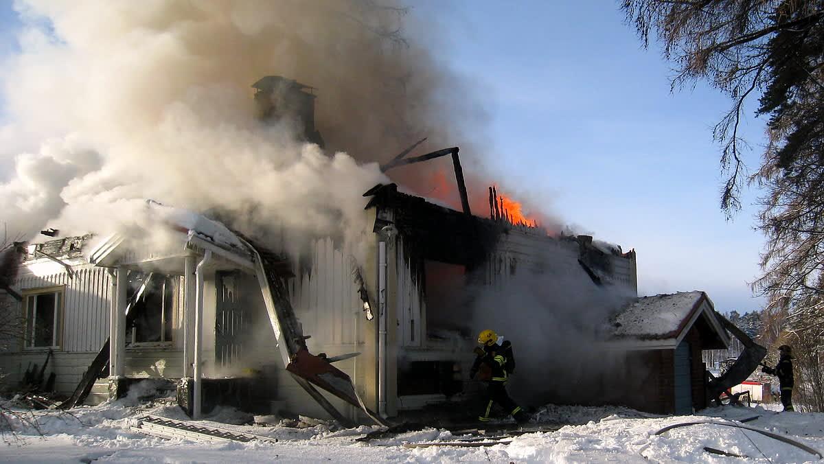 Palomiehiä palavan rakennuksen äärellä