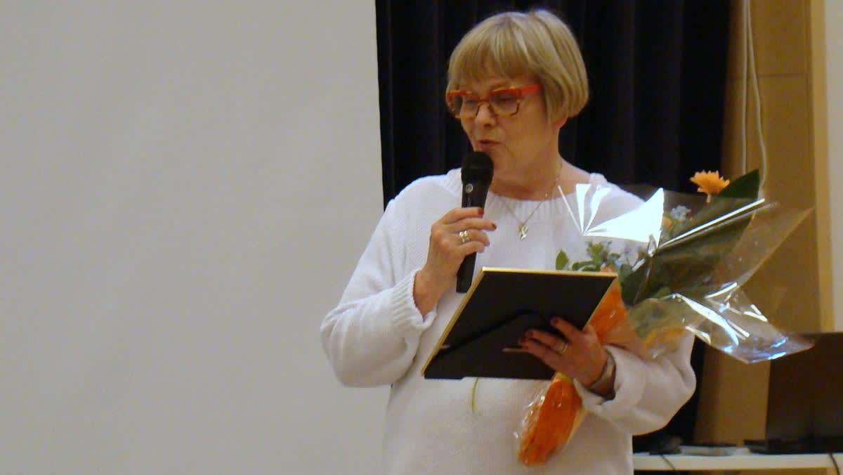 Vaaleanhiuksinen nainen pitämässä puhetta