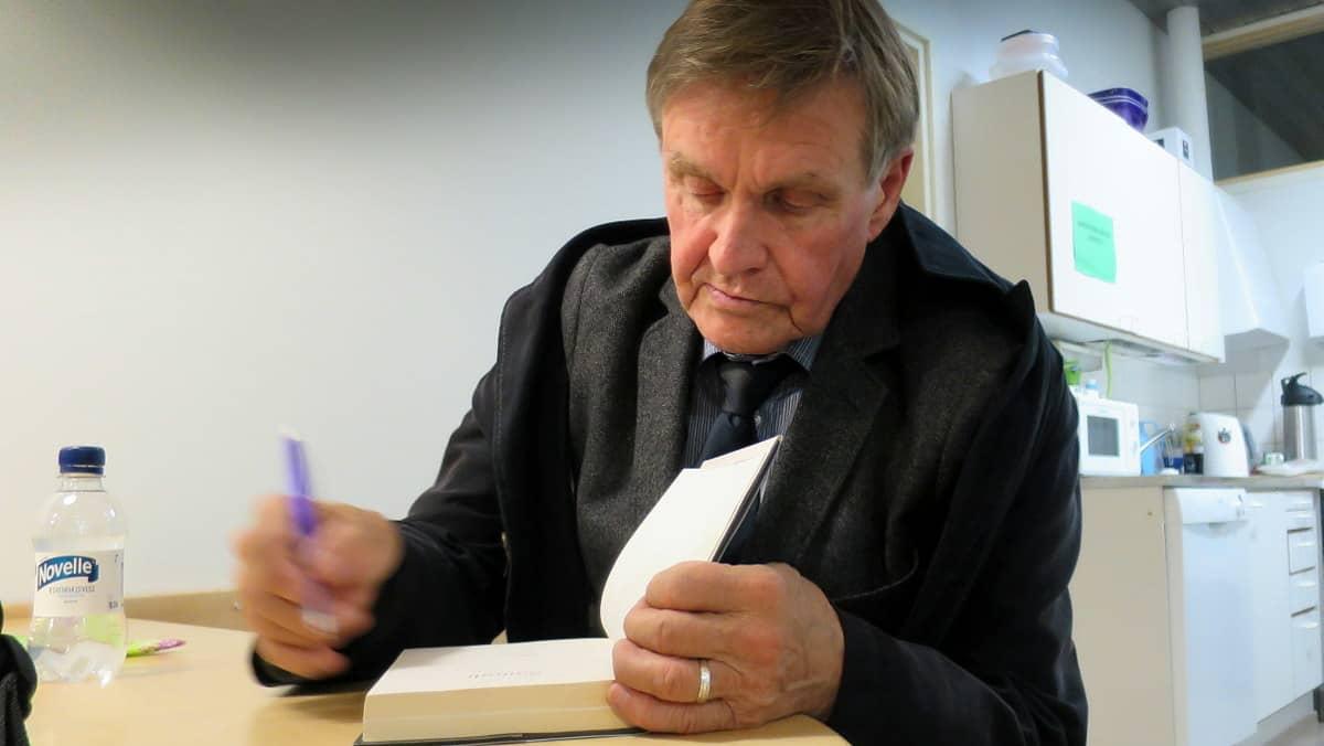 Mies kirjoittaa kirjan sisälehdelle omistuskirjoitusta