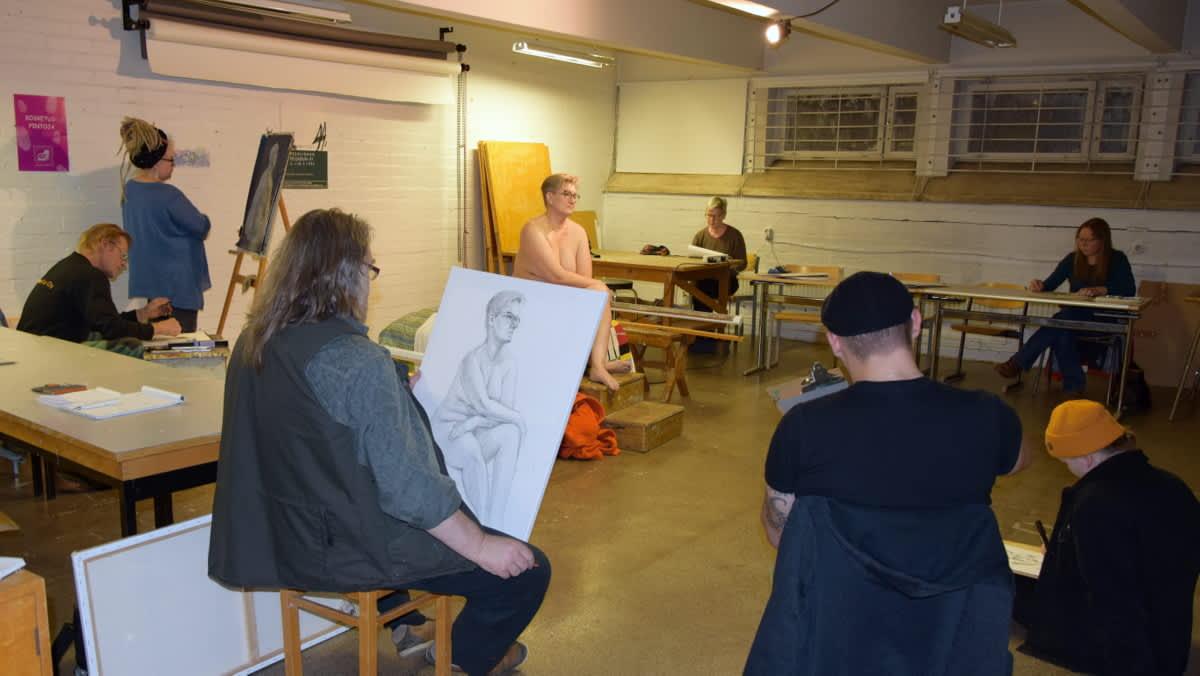 nainen istuu alastomana ja mies ja naispiirtäjiä on ympärillä