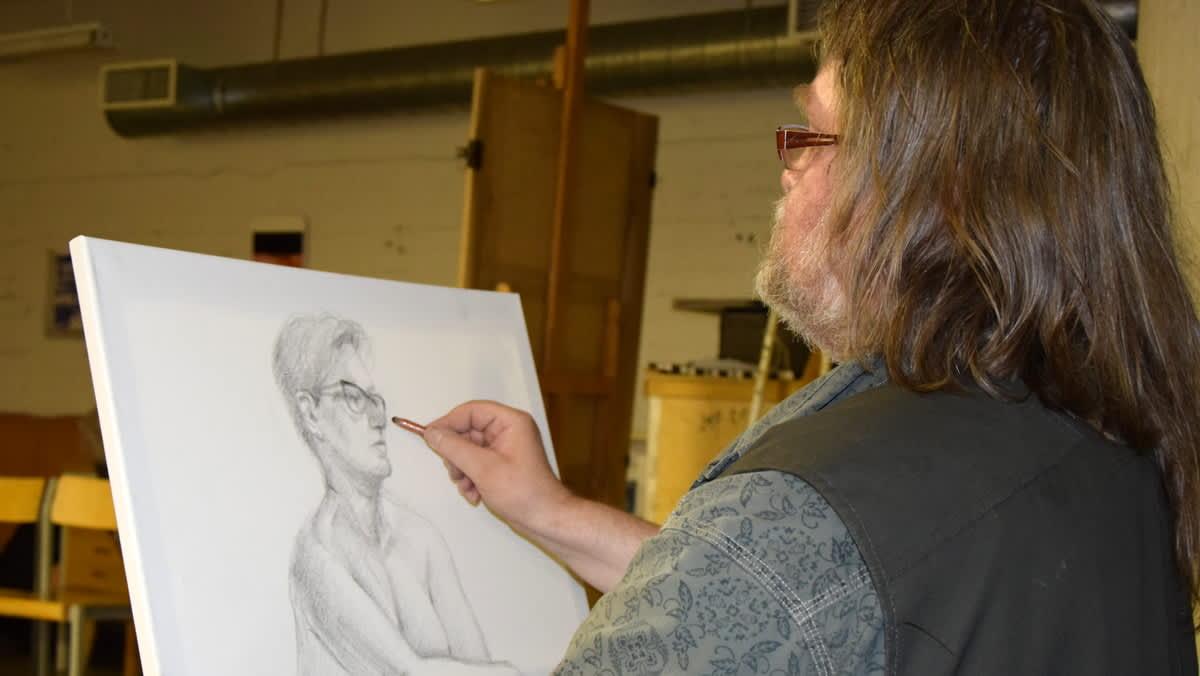 Mies piirtää lyijykynällä alastonta naista