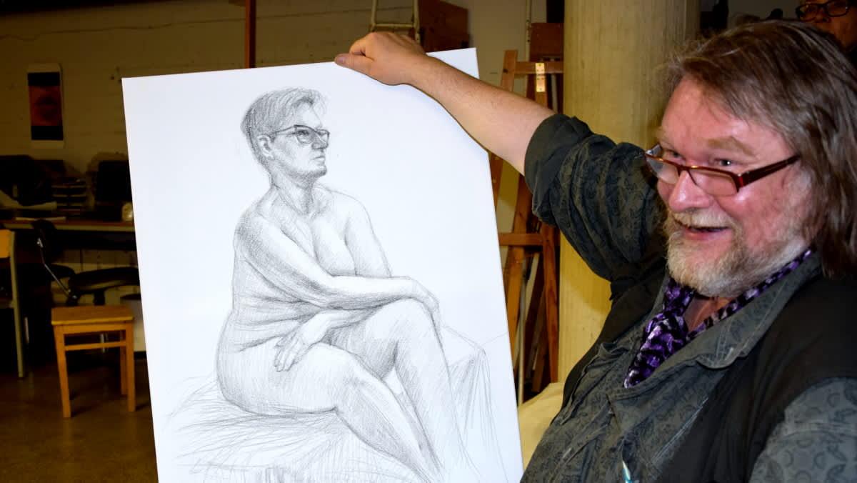 Mies esittelee lyijykynällä piirrettyä alastonmallin kuvaa