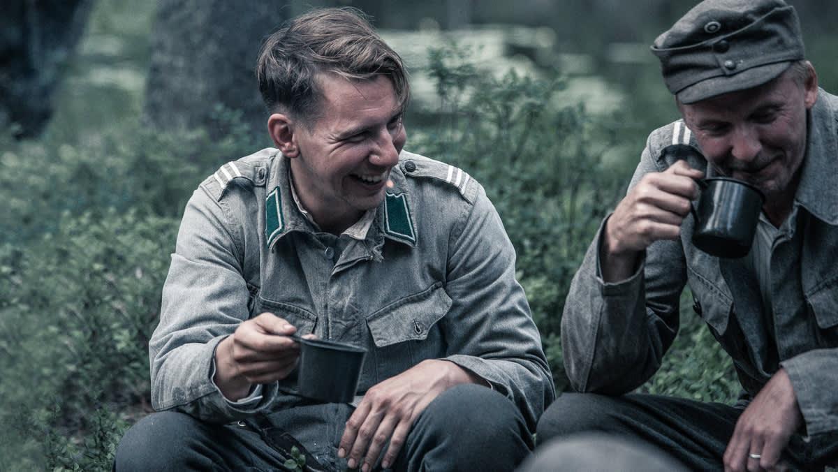 Miehet harmaissa palveluasuissa istuvat näreikössä ja juovat nauireskellen korviketta metallimukeista