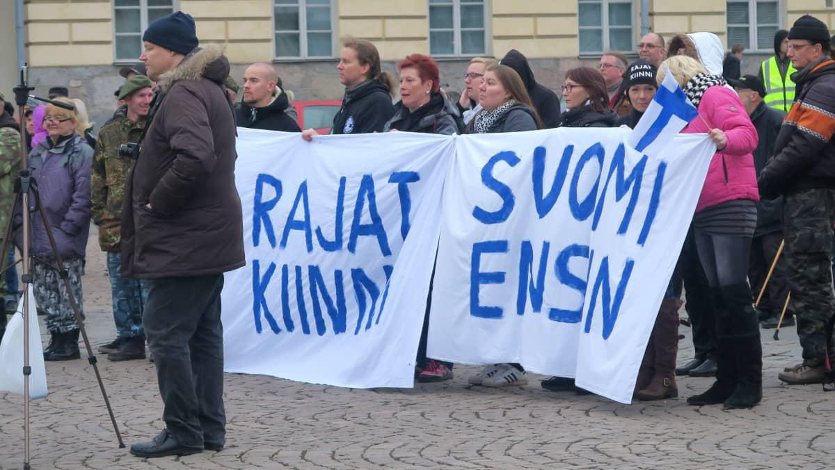 Mielenosoittajat pitävät lakanoita, joissa tekstit rajat kiinni ja Suomi ensin