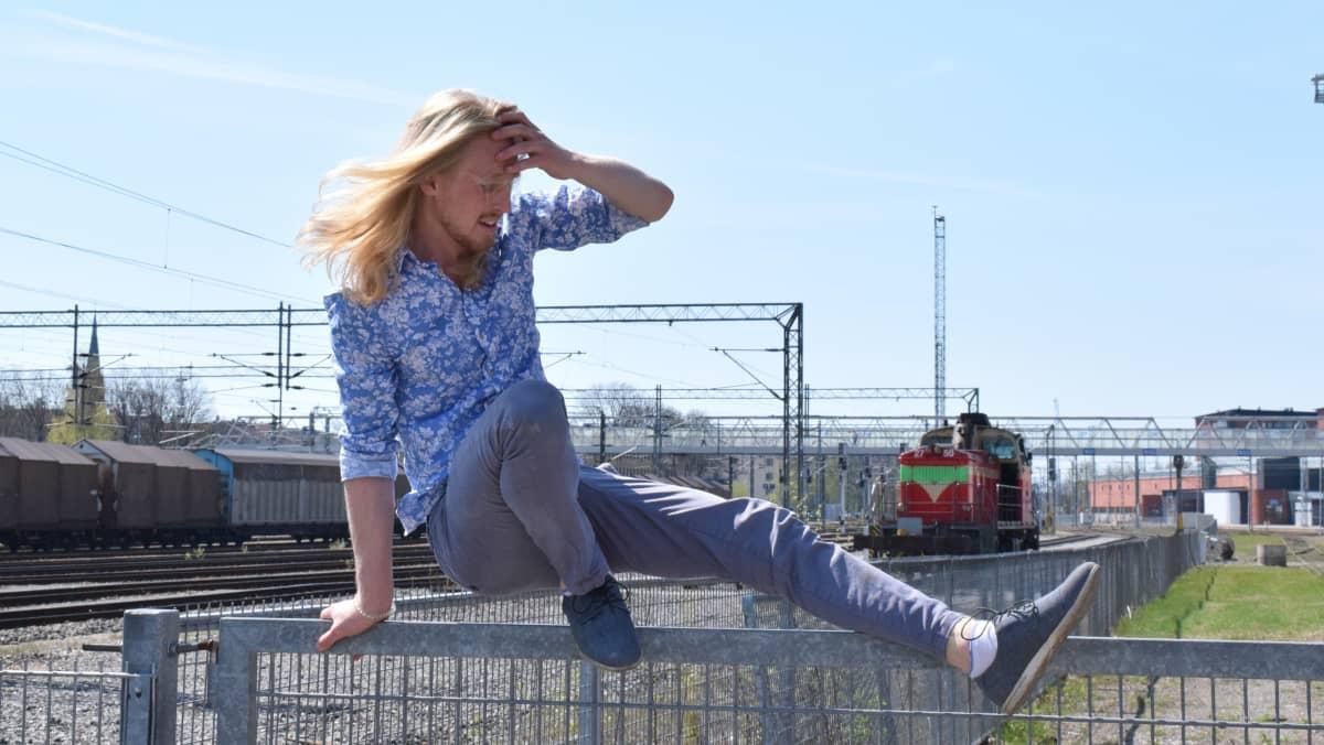 mies tasapainoilee kaiteella junanradan vieressä