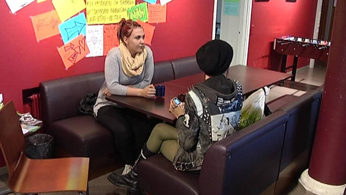 Kaksi tyttöä istuvat nuorisokahvilan pöydässä.