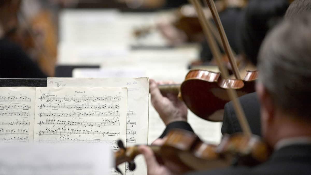 Mies soittaa viulua orkesterin mukana.