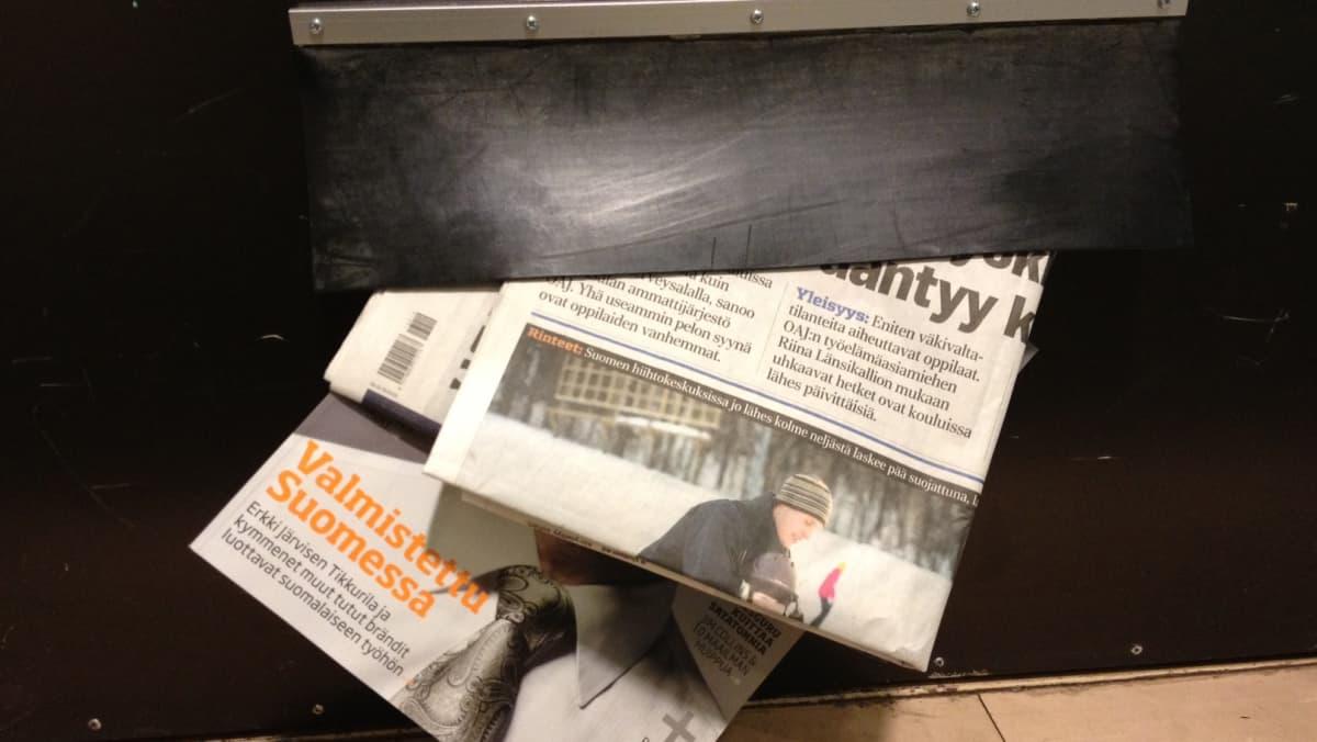 Sanomalehtiä ja aikauslehti postiluukussa