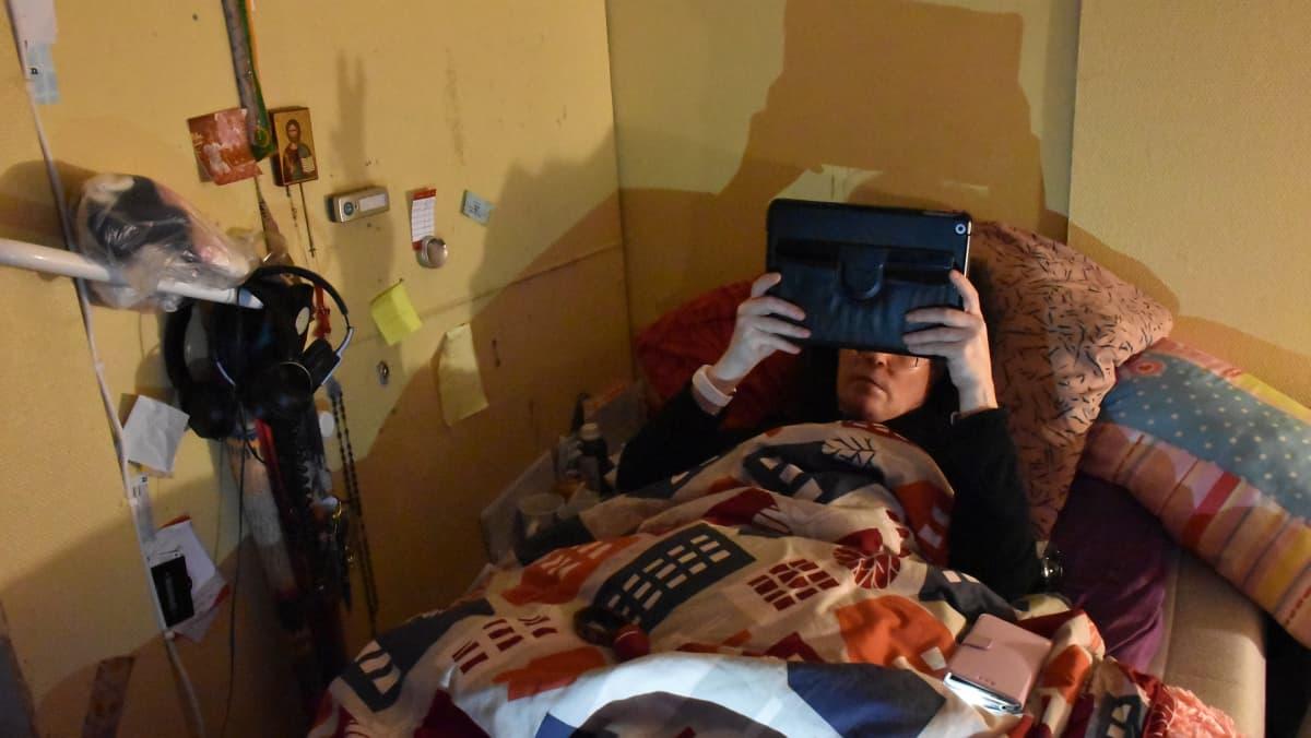 Nainen lukee läppäriä sängyssään.