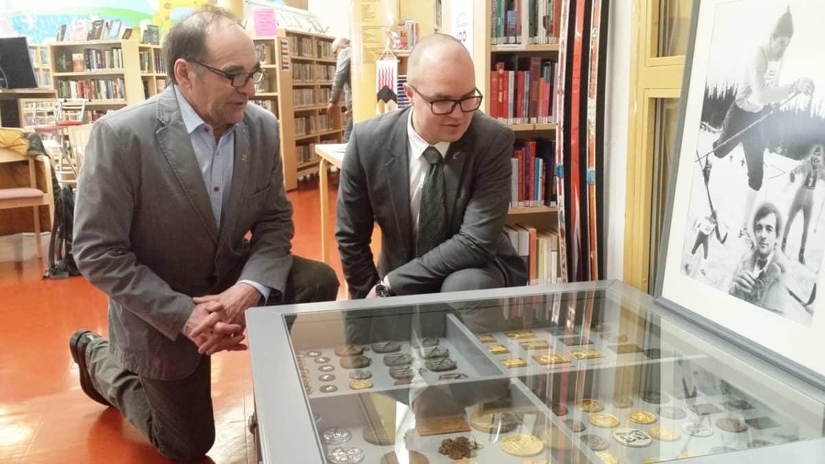 Kolarin kunnanjohtaja Antti Määttä ja Pertti Teurajärvi katselevat mitaleita Kolarin kirjastossa