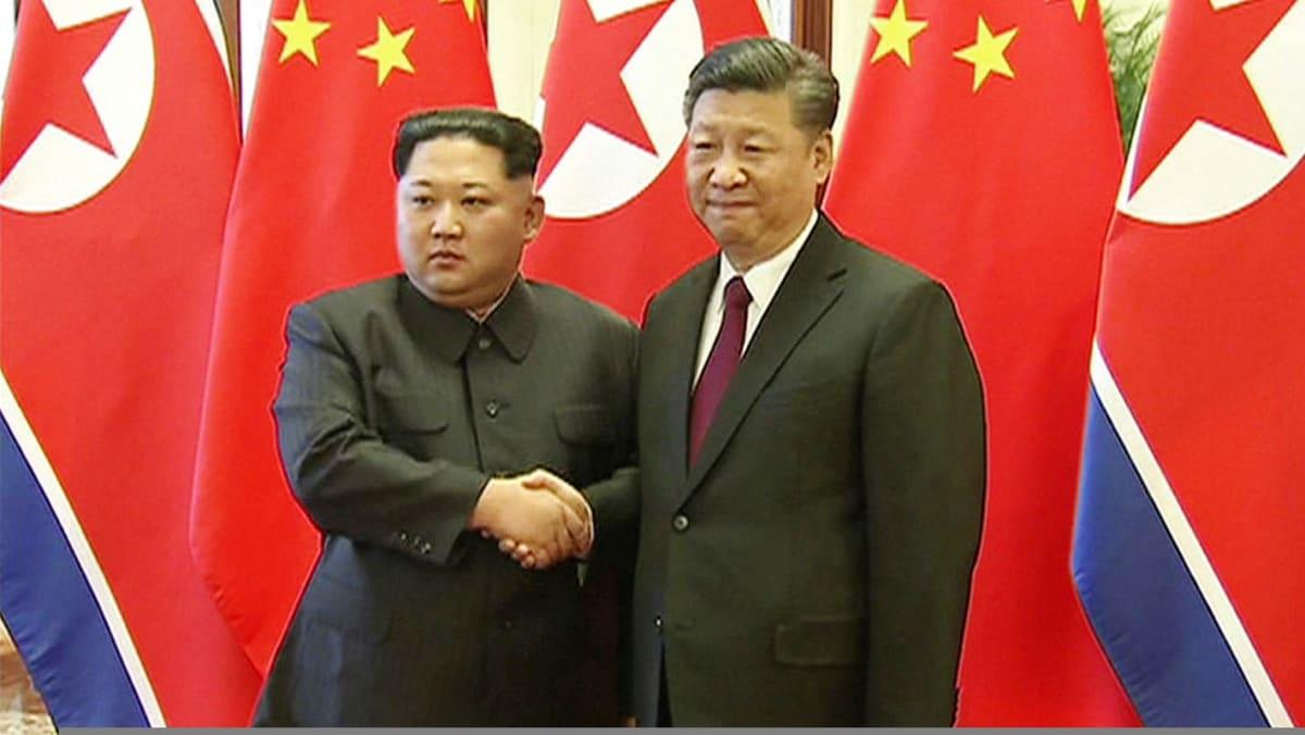 Kim Jong-un ja Xi Jinping kättelevät Pekingissä.