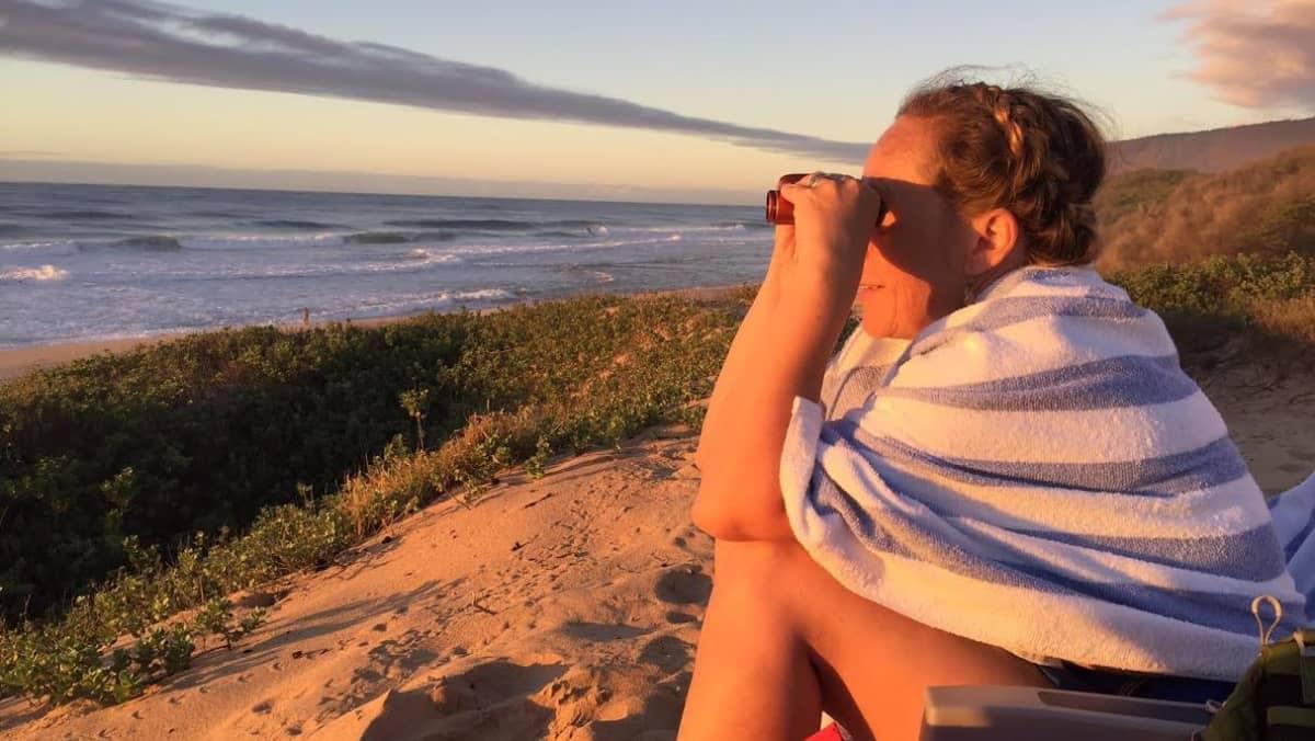 nainen istuu rannalla ja kiikaroi merelle