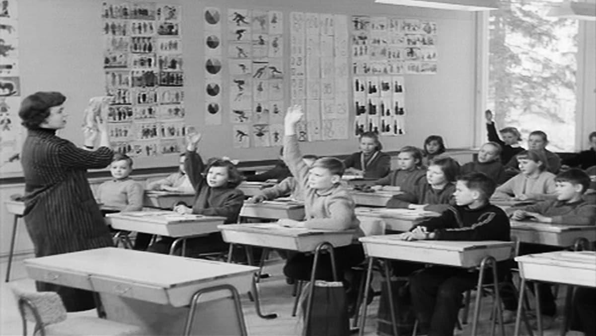 Oppilaita ja opettaja luokkahuoneessa, opettaja näyttää paperia ja oppilaista osa viittaa.
