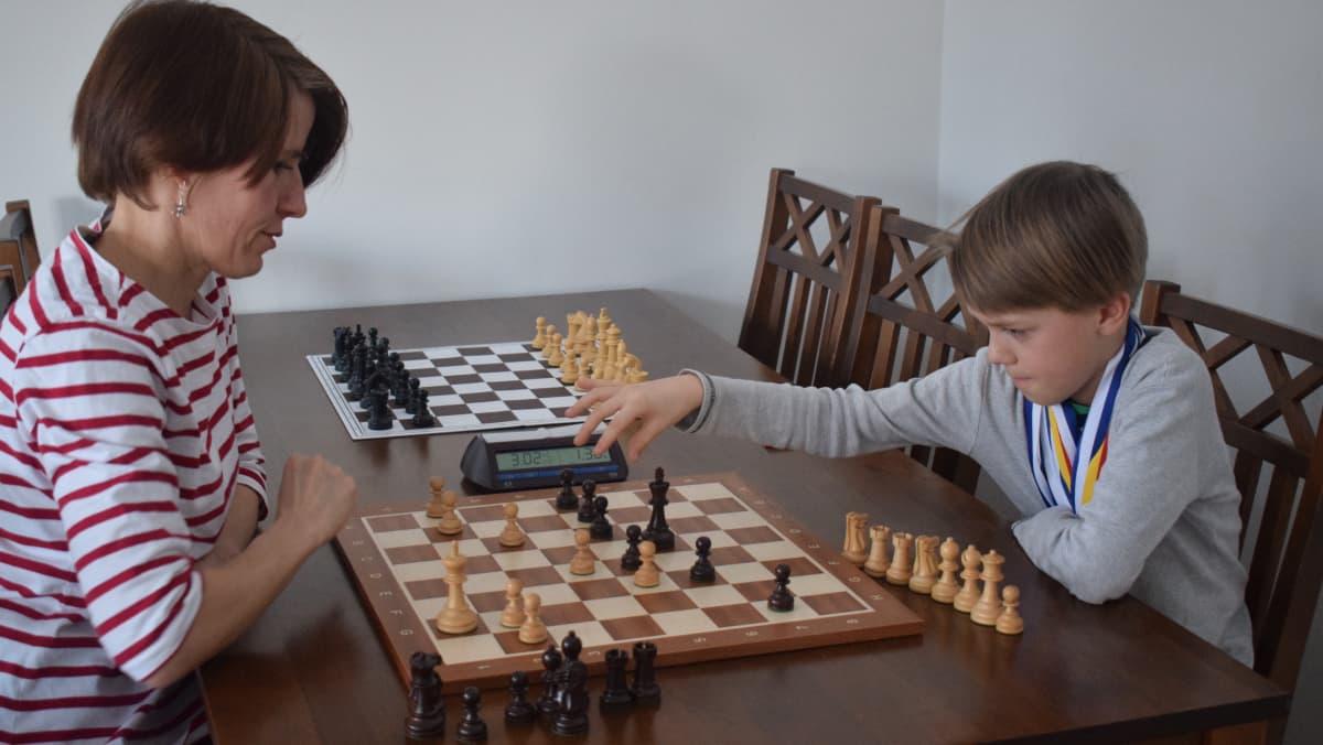 Äiti ja poika pelaavat shakkia