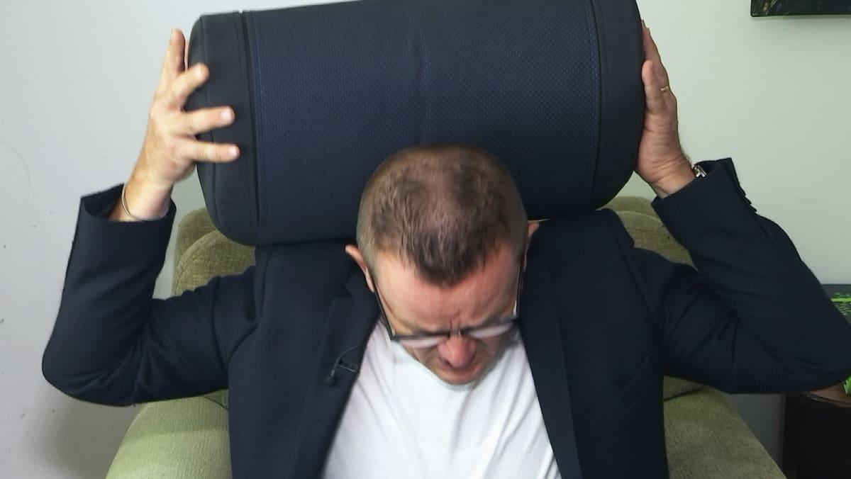 Toimittaja Matti Toivonen nostaa Humu-äänityynyä niskansa taakse nojatuolissa.