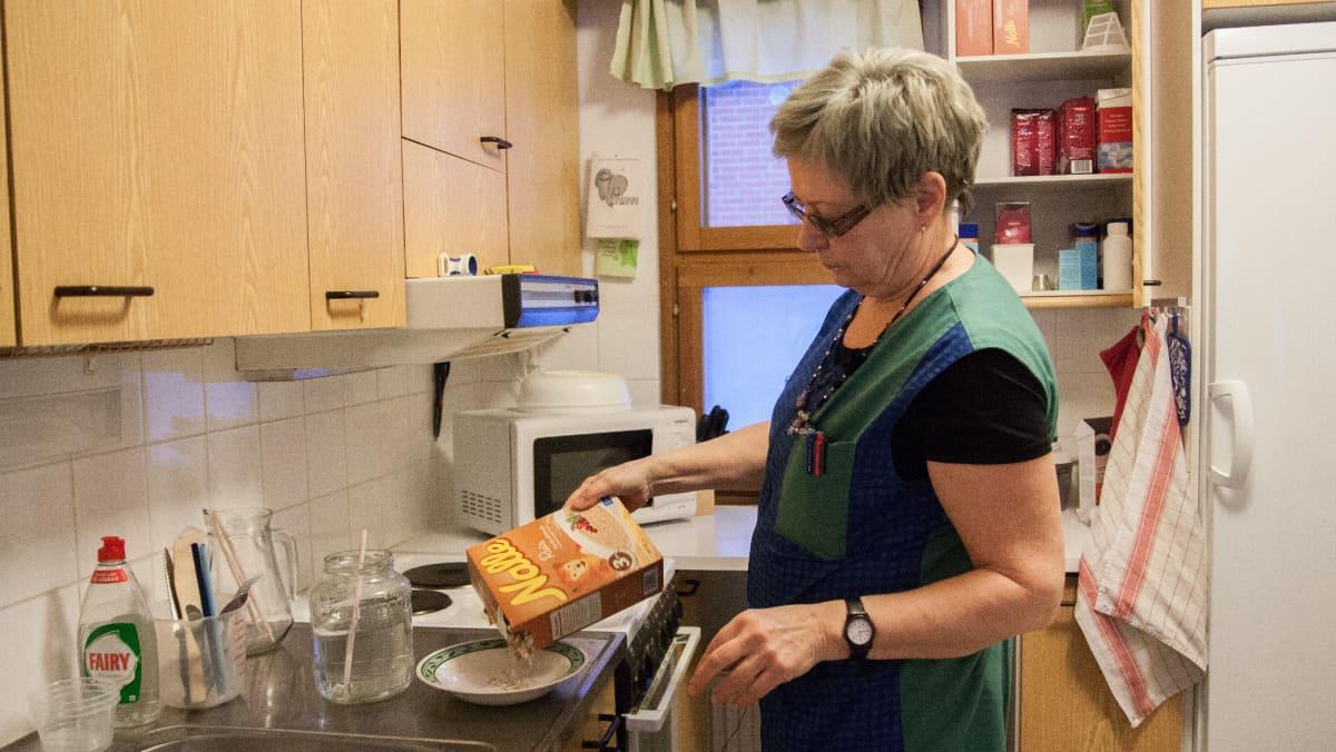 Hyrynsalmelainen kotihoitaja Paula Keränen tekee puuroa vanhuksen keittiössä.