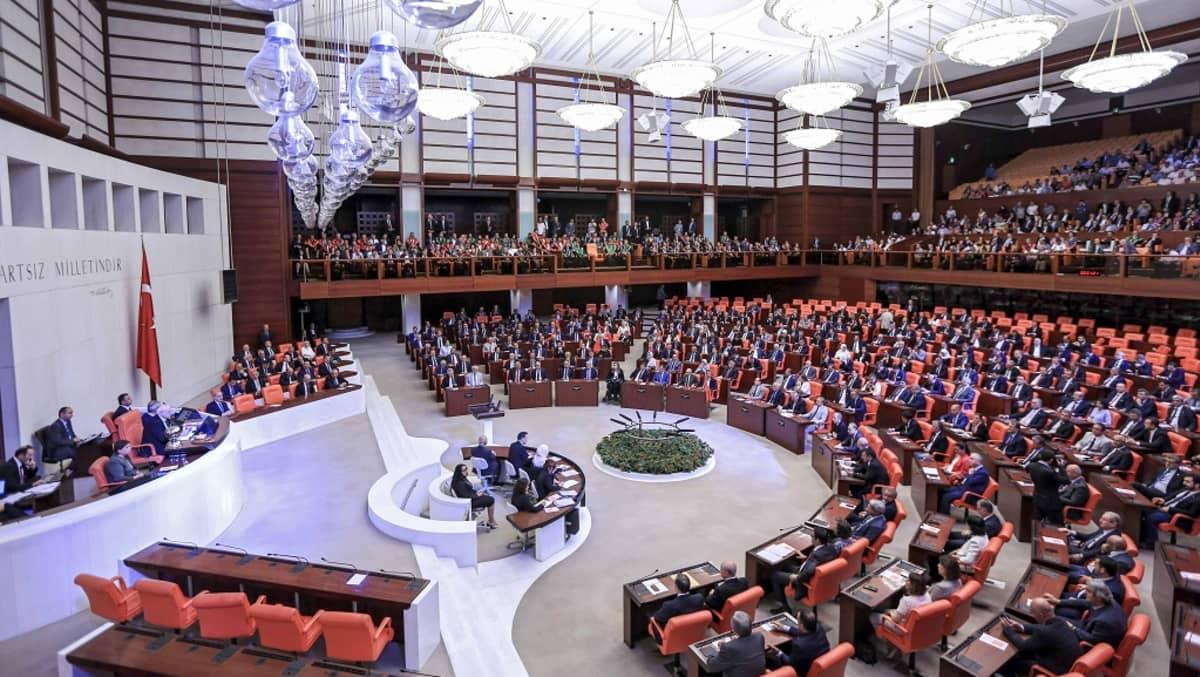 Turkin parlamentin istuntosali, jossa kansanedustajat istuvat puoliympyrän muotoon asetettujen paripöytien takana.