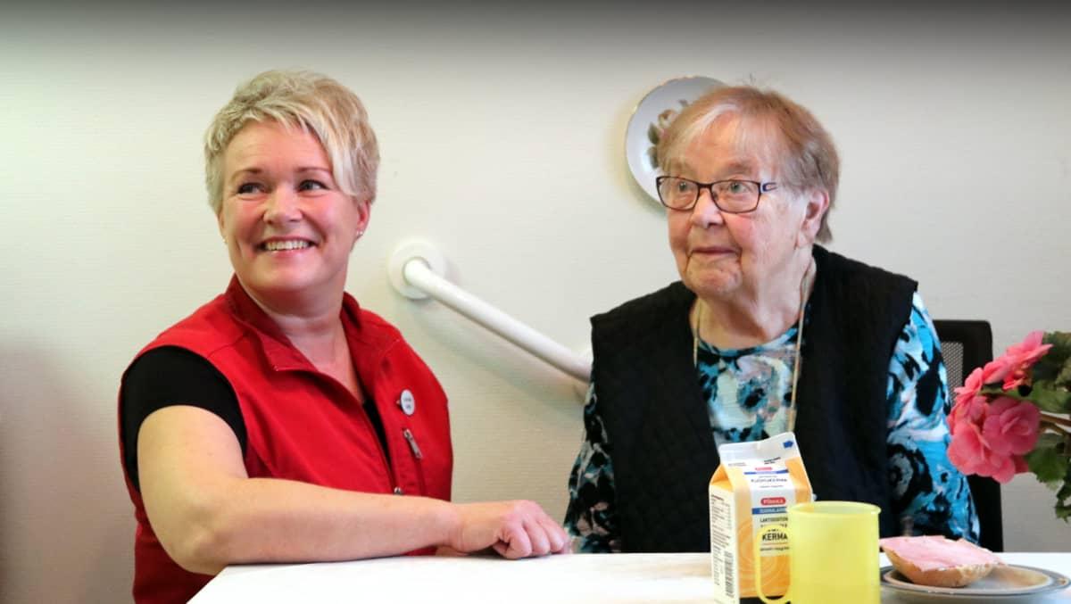 Kotihoitaja Anne Helander ja asiakas Eeva Holappa istuvat aamukahvipöydässä.