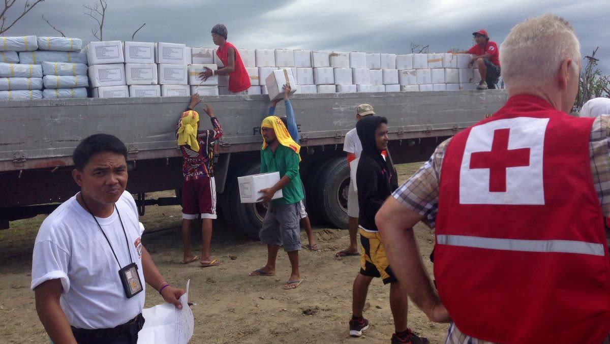 Ihmiset purkavat avustuspaketteja rekasta