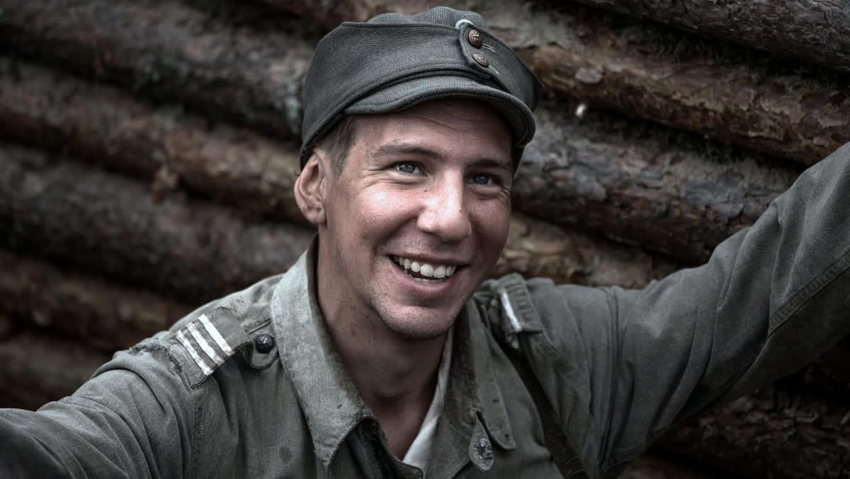 Mies vanhassa asepuvussa nauraa juoksuhaudassa