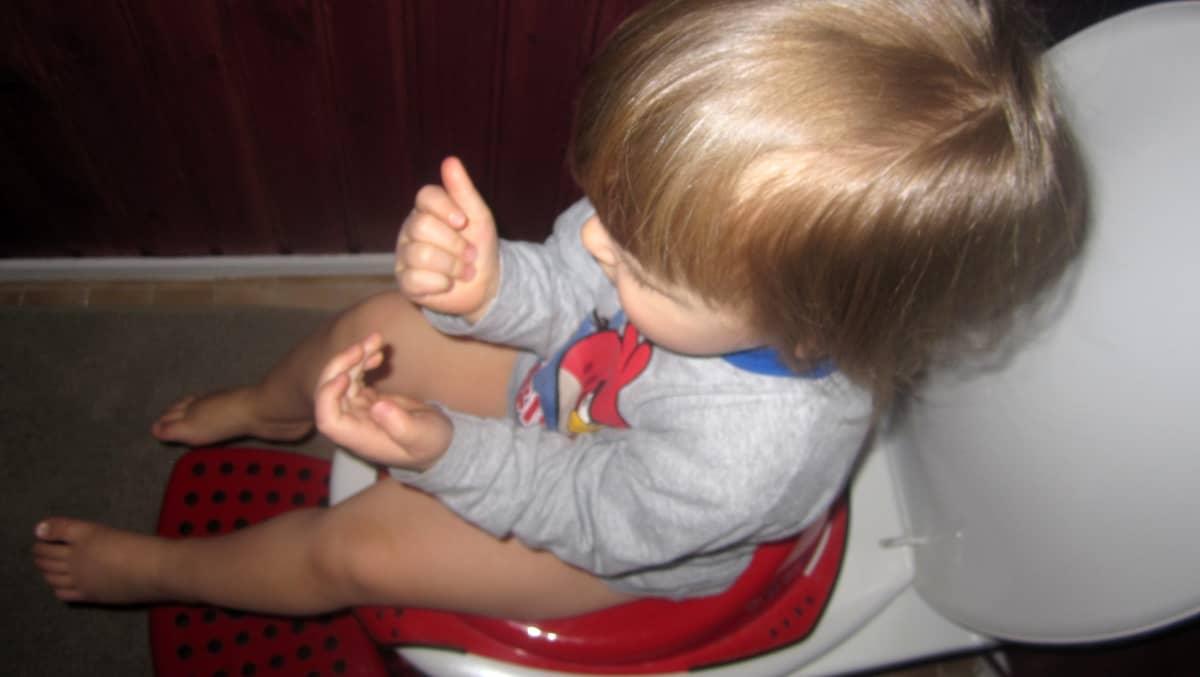 Poika istuu pöntöllä