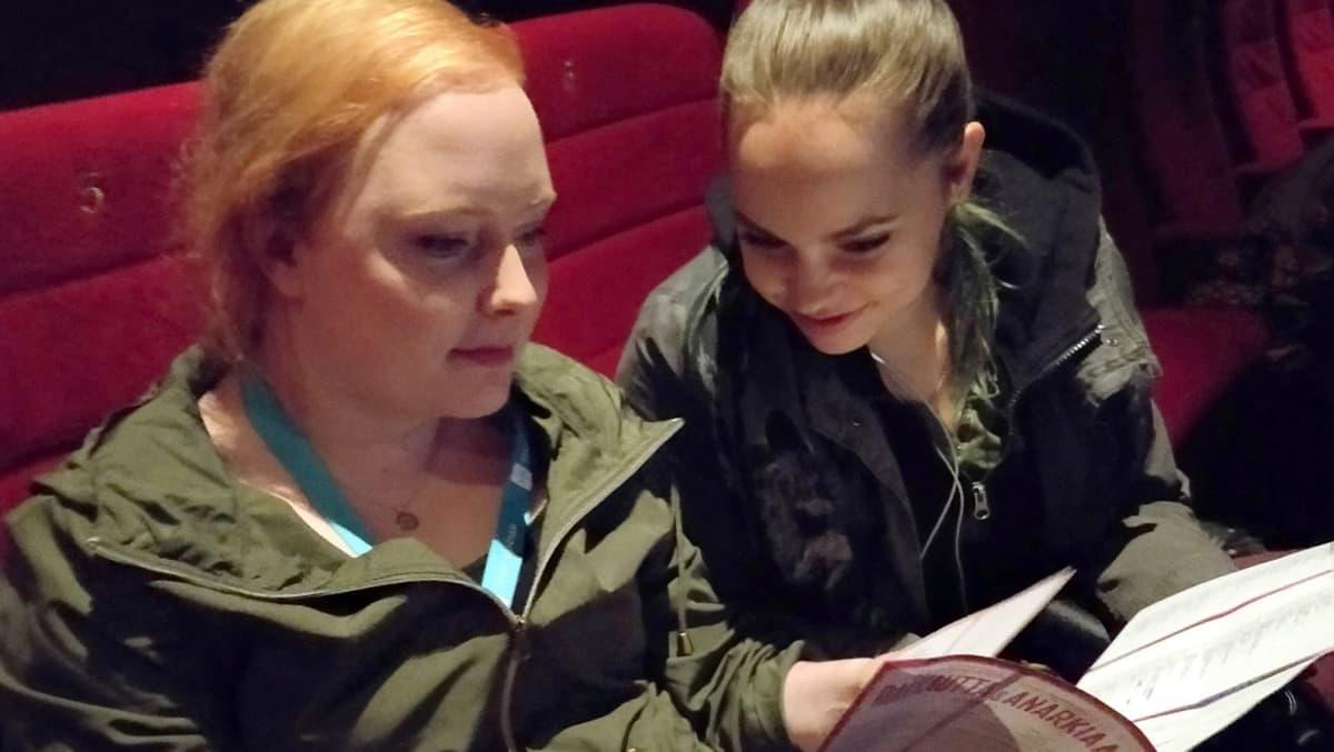 Kaksi naista istuvat leffateatterissa ja tutkivat elokuvafestivaalin ohjelmakarttaa.