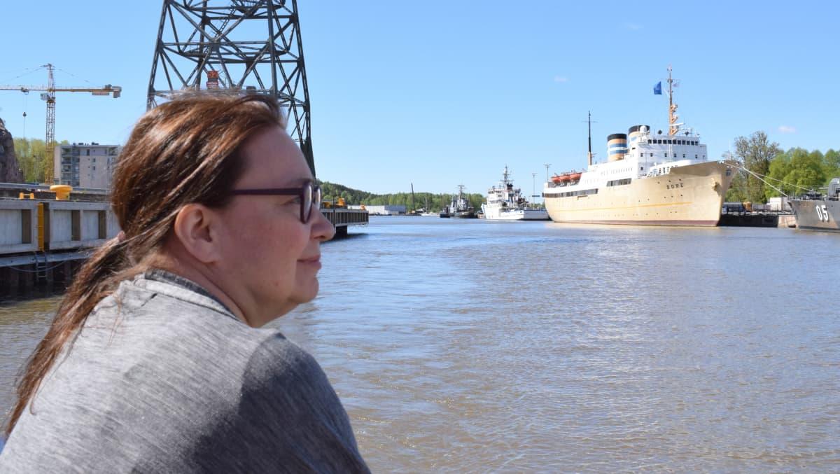 nainen laivan kyydissä, taustalla isoja laivoja