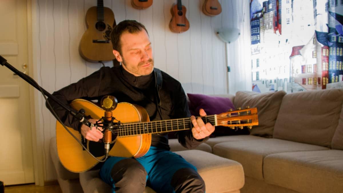 Janne Koskela kotonaan soittamassa itse valmistamaansa kitaraa.